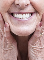 An up-close image of an older woman holding her face between her hands after receiving her customized dentures in Norwood