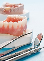 A mouth mold that contains a customized denture and dental instruments lying next to it