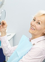 An older woman holding a handheld mirror at the dentist's office and smiling