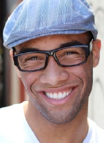 Man with glasses and hat smiling