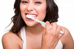 woman brushing her teeth smiling